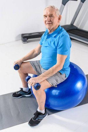 high angle view of smiling senior man with dumbbells sitting on fitness ball on grey backdrop