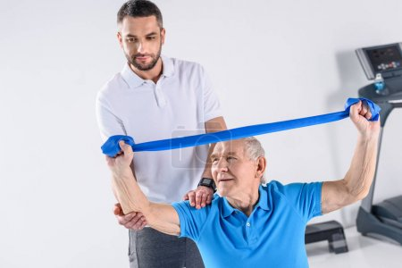 rehabilitation therapist assisting senior man exercising with rubber tape