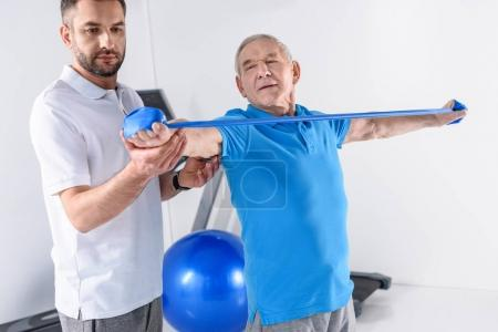portrait of rehabilitation therapist assisting senior man exercising with rubber tape