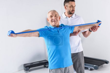 rehabilitation therapist assisting smiling senior man exercising with rubber tape