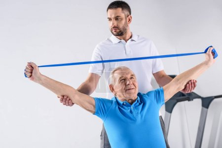 portrait of rehabilitation therapist assisting senior man exercising with rubber tape