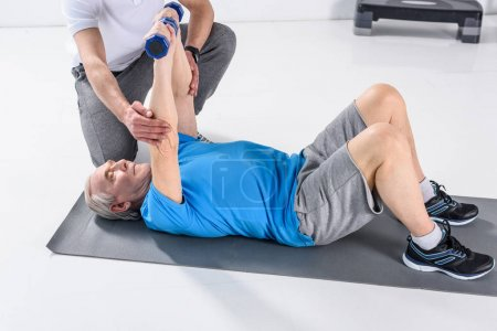 partial view of rehabilitation therapist assisting senior man exercising with dumbbells on mat