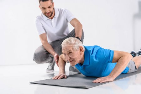 rehabilitation therapist helping senior man exercising on mat on grey background