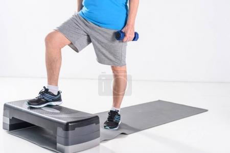 partial view of senior man with dumbbells exercising on stepper isolated on grey