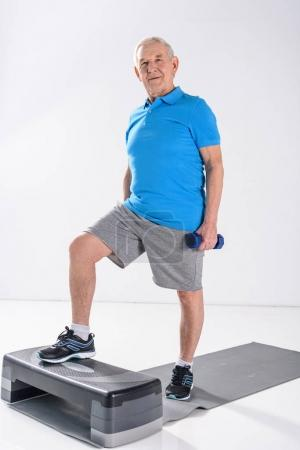 senior man with dumbbells exercising on stepper isolated on grey