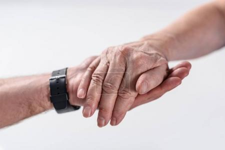 cropped shot of senior man and rehabilitation therapist holding hands isolated on grey