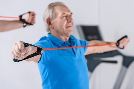 selective focus of senior man exercising with rubber tape