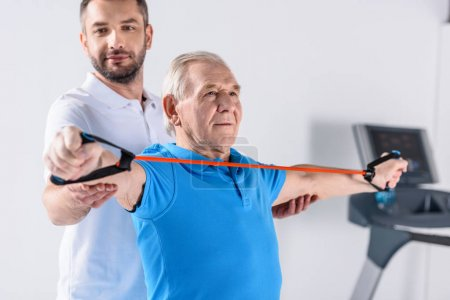 smiling rehabilitation therapist assisting senior man exercising with rubber tape