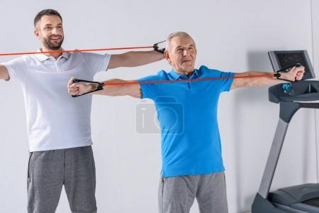 smiling rehabilitation therapist and senior man exercising with rubber tapes