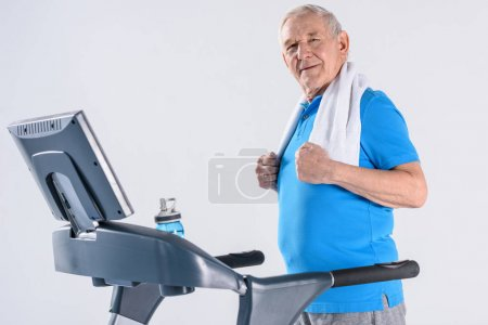 side view of smiling senior man with towel exercising on treadmill isolated on grey