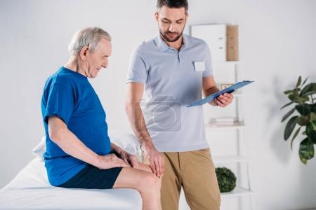 rehabilitation therapist with notepad checking senior mans knee on massage table