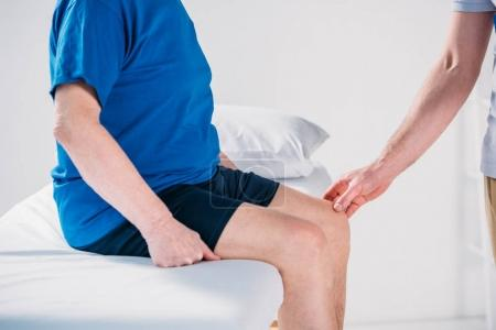 cropped shot of rehabilitation therapist checking senior mans knee on massage table