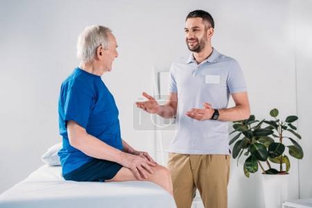 smiling rehabilitation therapist and senior man on massage table having conversation
