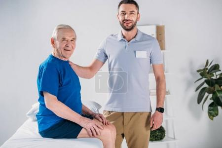 portrait of rehabilitation therapist and smiling senior man on massage table