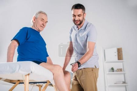 rehabilitation therapist with reflex hammer checking senior mans knee on massage table