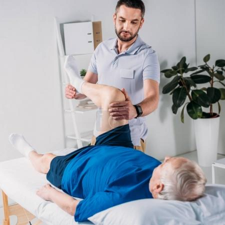 focused rehabilitation therapist massaging senior mans leg on massage table