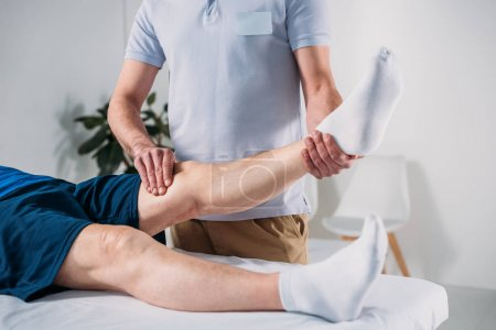 cropped shot of physiotherapist massaging senior mans leg on massage table