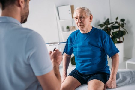 cropped shot of rehabilitation therapist with notepad and senior man on massage table