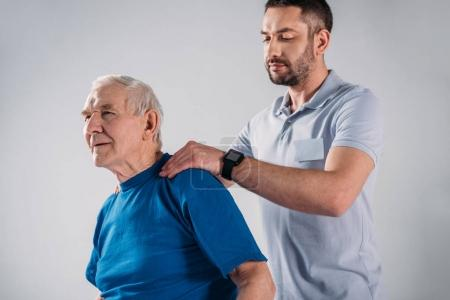 physiotherapist doing massage to senior man isolated on grey