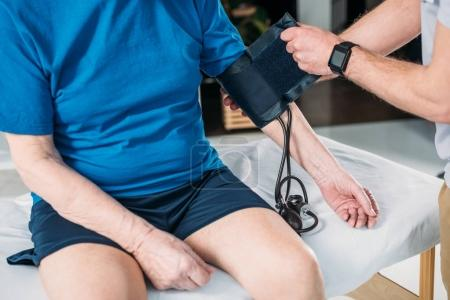 partial view of rehabilitation therapist measuring pressure of senior man on massage table