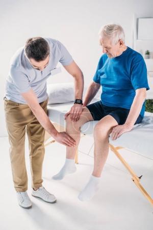 rehabilitation therapist doing massage to senior man on massage table