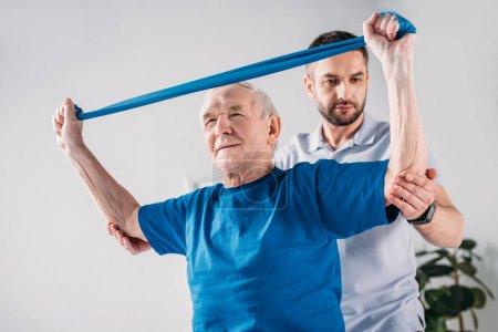 focused rehabilitation therapist assisting senior man exercising with rubber tape