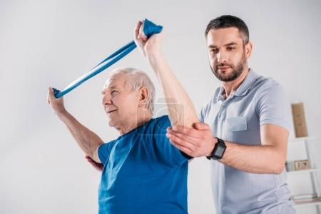 side view of rehabilitation therapist assisting senior man exercising with rubber tape