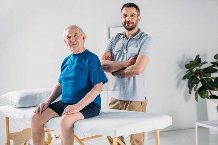 rehabilitation therapist with stethoscope and senior man on massage table
