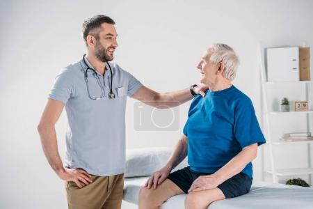 rehabilitation therapist with stethoscope and smiling senior man on massage table