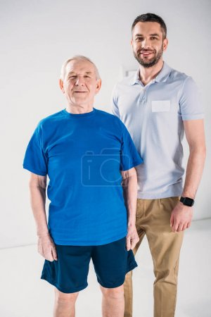 portrait of smiling senior man and rehabilitation therapist looking at camera on grey backdrop