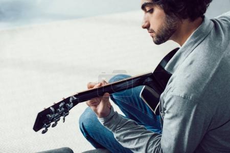 Photo pour Bel homme jouant de la guitare acoustique à la maison - image libre de droit