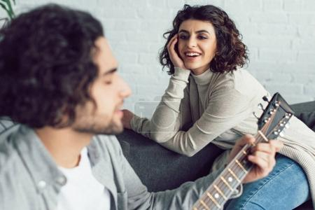 boyfriend playing guitar and singing for smiling girlfriend at home