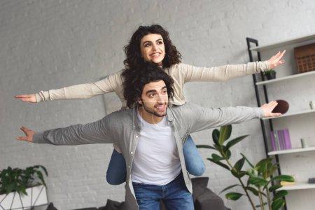 Photo pour Piggyback donnant copain à rire de petite amie et ils ont fait semblant de voler à la maison - image libre de droit