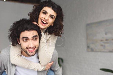 Freund gibt lachende Freundin zu Hause Huckepack