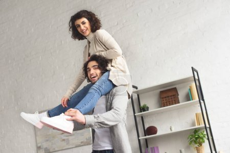 smiling girlfriend sitting on boyfriends shoulders at home