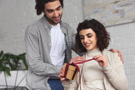 boyfriend presenting gift to girlfriend at home