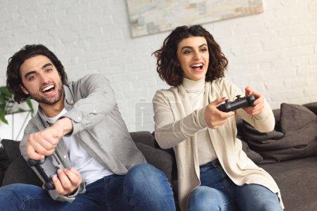 Foto de Pareja joven jugando videojuegos en su casa de risa - Imagen libre de derechos