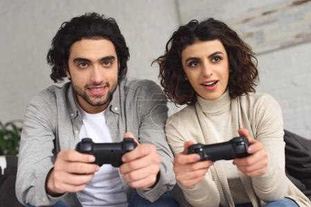 Photo for Excited young couple playing video game with joysticks at home - Royalty Free Image