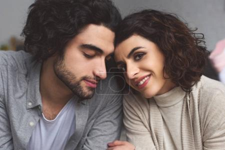 tender affectionate couple touching with foreheads at home