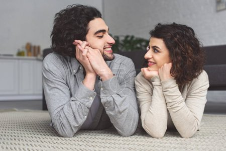 Photo for Smiling young couple lying on floor and looking at each other at home - Royalty Free Image
