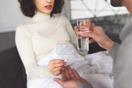 cropped image of boyfriend giving pill and glass of water to sick girlfriend at home