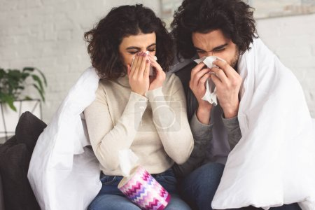 sick young couple blowing noses into napkins at home