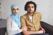 muslim couple sitting on sofa in living room and looking at camera