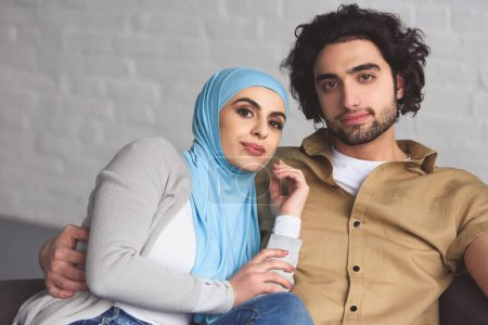 happy muslim couple sitting on sofa in living room and looking at camera