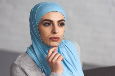 portrait of pensive beautiful muslim woman in hijab looking away at home