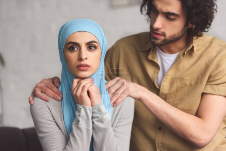 muslim boyfriend hugging worried girlfriend in hijab in living room