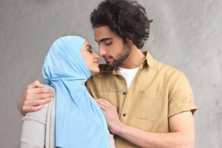 tender muslim couple going to kiss at home