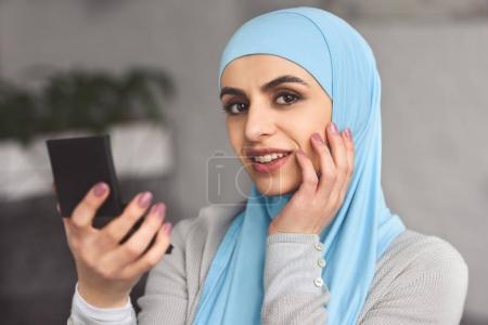 Photo pour Souriante belle femme musulmane en hijab tenir le miroir à la maison - image libre de droit