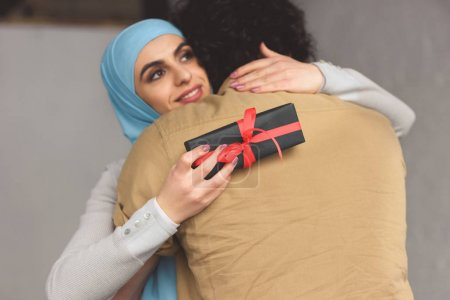 muslim girlfriend in hijab holding present box and hugging boyfriend at home