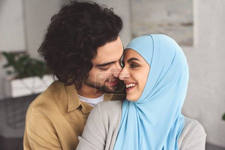 smiling muslim couple hugging and touching with noses at home